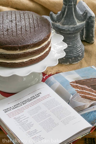 Chocolate Cake with Vanilla Buttercream Filling unfrosted on a cake stand next to an open cookbook
