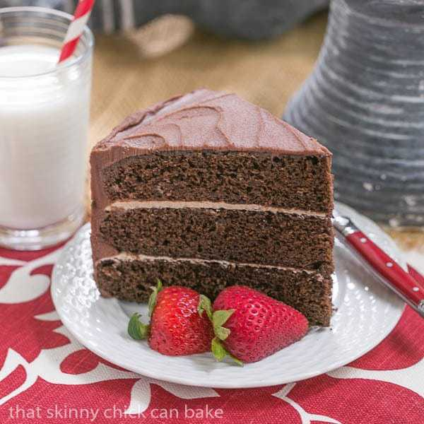 Slice of Chocolate Layer Cake with Vanilla Buttercream on a white plate with strawberries