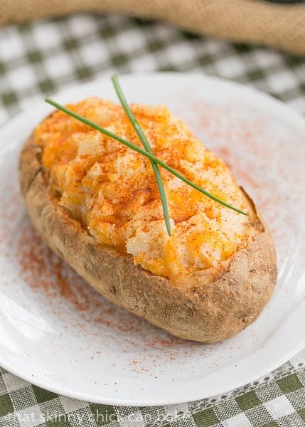 Overhead view of a Twice Baked Potato topped with chives on a white plate