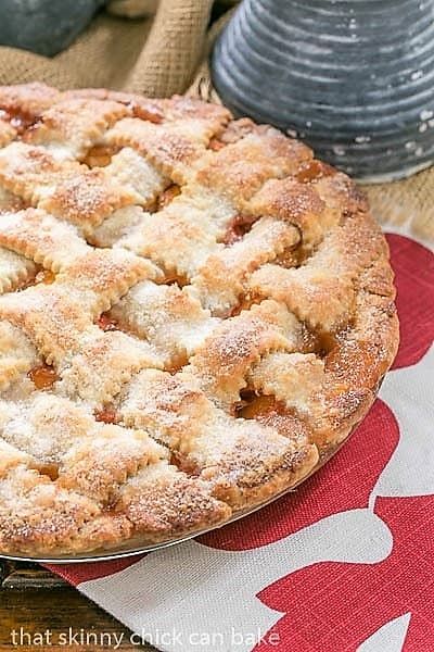 Classic Peach Pie with a lattice crust on a red and white napkin