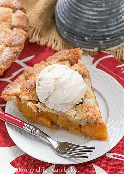 A slice of Classic Peach Pie on a white plate with a scoop of ice cream