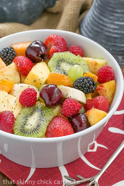 Honey Lime Fruit Salad in a white serving bowl on a white and red napkin