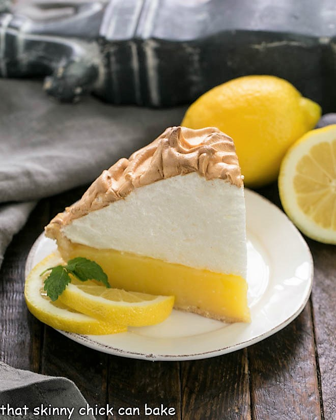 Slice of Mile High Lemon Meringue Pie on a white dessert plate garnished with lemon slices and mint sprigs