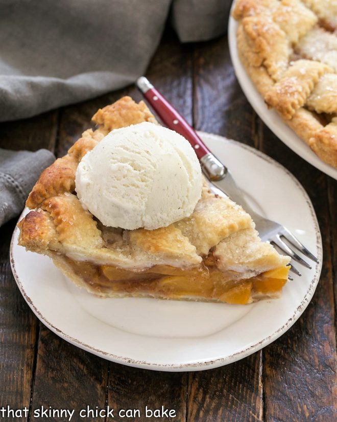 A slice of Peach Pie on a white plate with a scoop of ice cream