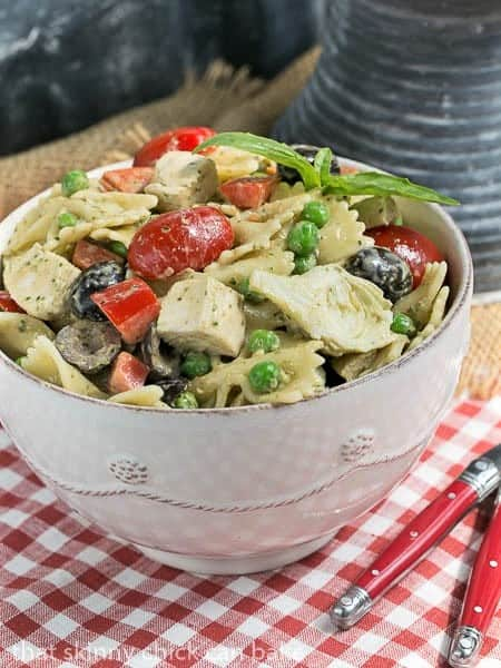 Pesto Pasta Salad in a white bowl with two red handled forks