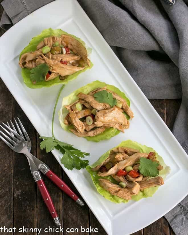 Overhead view of shredded chicken lettuce wraps on a white tray