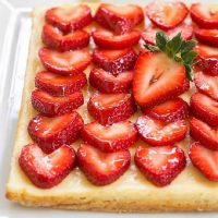 Cheesecake bars topped with strawberries on a white tray
