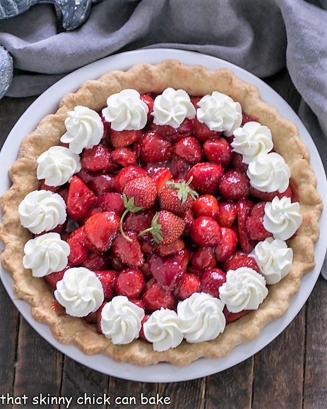 Overhead view of a fresh strawberry pie garnished with whipped cream