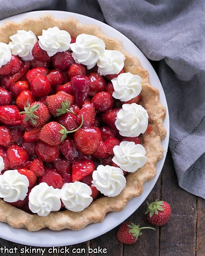 Partial overhead view of a strawberry pie with whipped cream garnishes