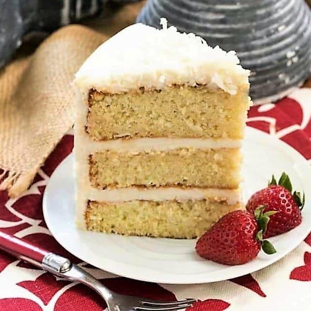 Italian Cream Cake slice on a white dessert plate with strawberry garnish