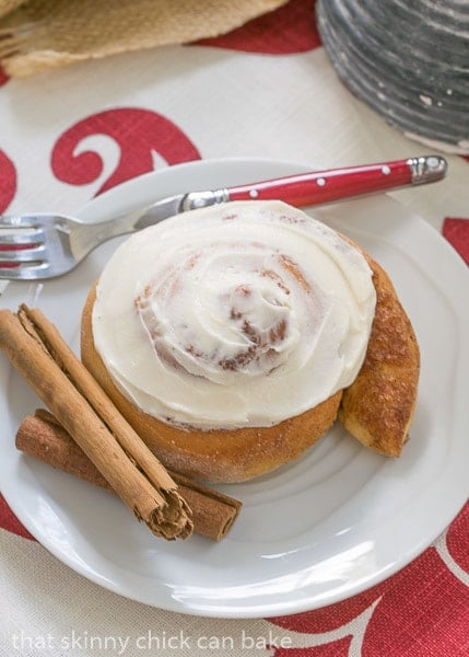 Old Fashioned Cinnamon Roll on a white plate with a red-handled fork