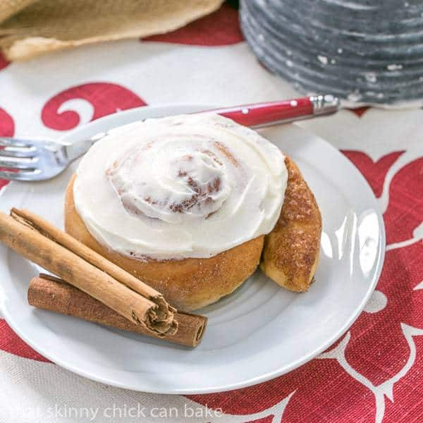 Old Fashioned Cinnamon Roll on a white plate with cinnamon sticks