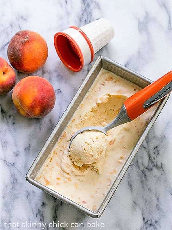 Fresh Peach Ice Cream in a loaf pan with an orange handled ice cream scoop