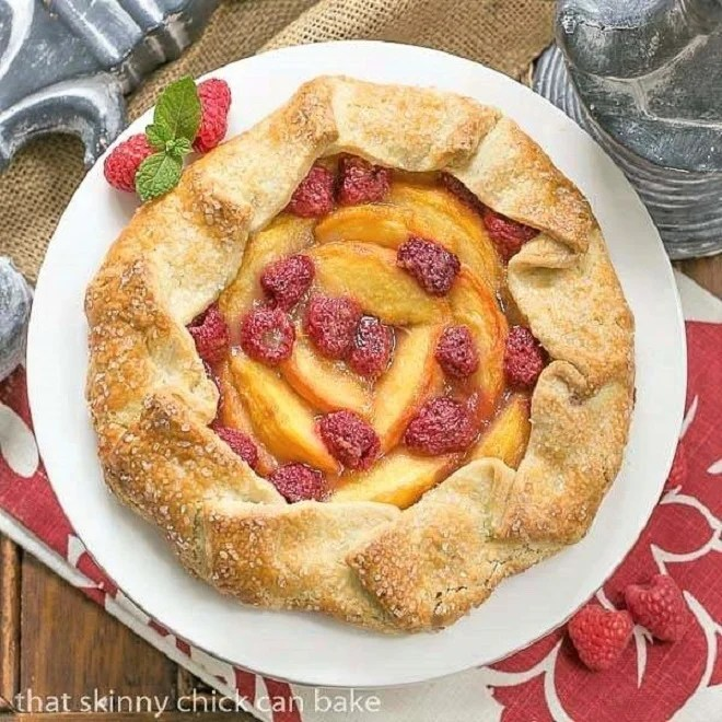 Peach Raspberry Galette on a white ceramic cake stand