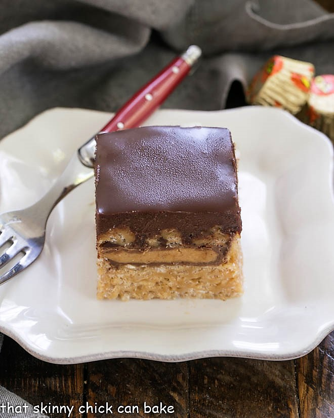 Stuffed Peanut Butter Rice Krispie Treats on a square white plate with a red handle fork