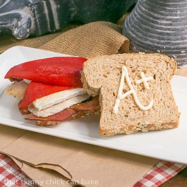 Roasted Chicken Brie and Bacon Sandwich on a white tray