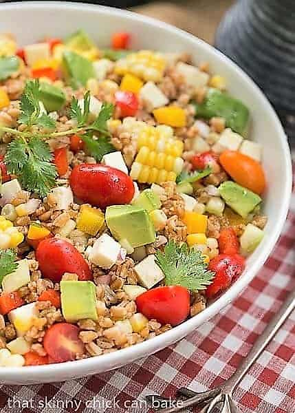 Summer Farro Salad in a white bowl over a checked napkin