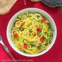 Zucchini Noodles with Parmesan in a white bowl on a red napkin
