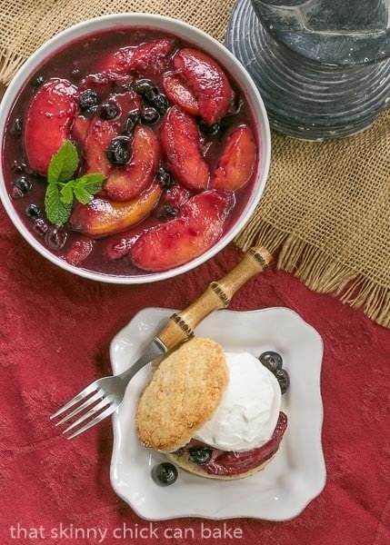 Overhead view of Blueberry Peach Shortcakes with a bowl of macerated peaches and blueberries