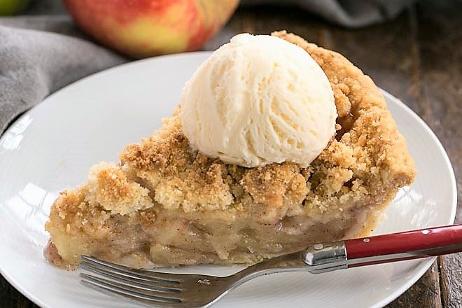 Slice of the best apple pie recipe topped with ice cream on a white plate