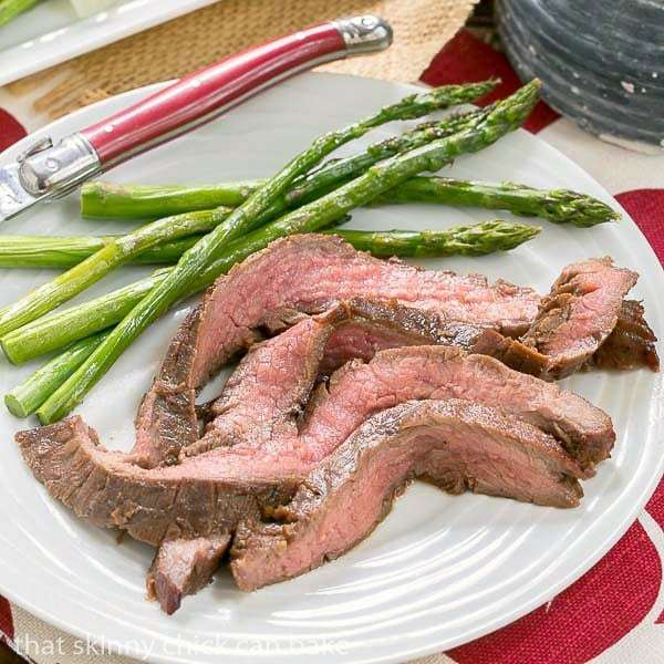 Easy Grilled Flank Steak slices on a white dinner plate with aspargus