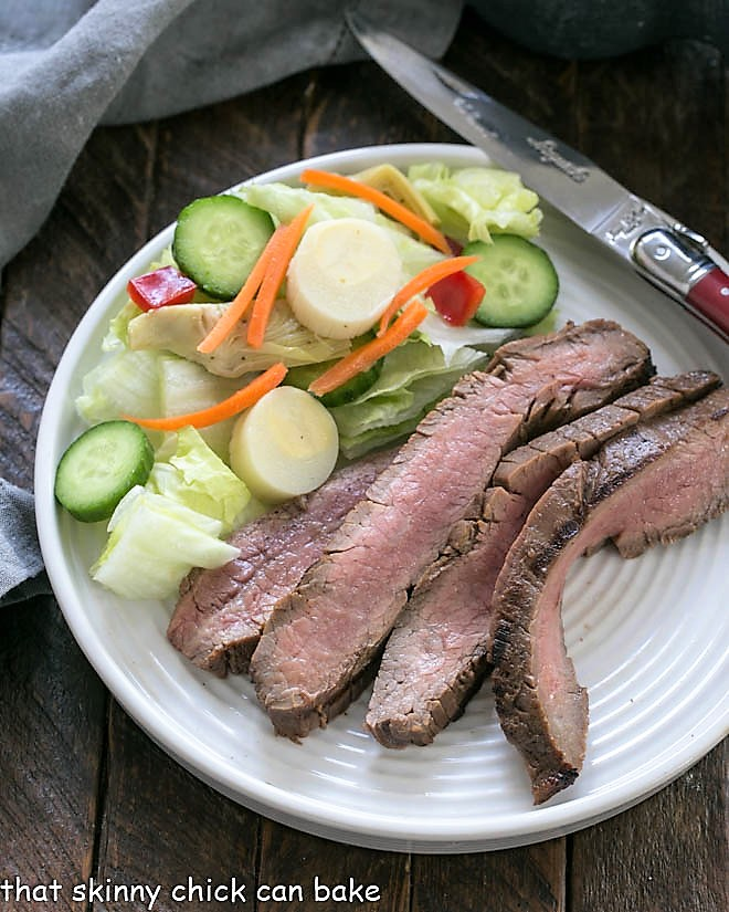 Overhead view of Easy Grilled Flank Steak on a dinner plate with a green salad