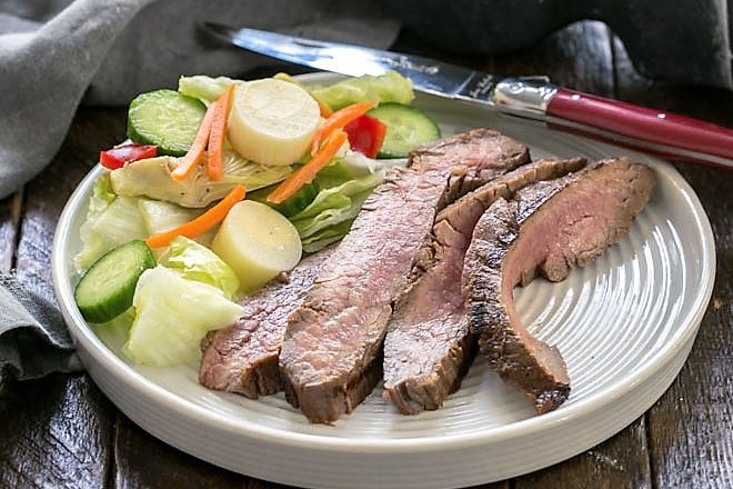 Slices of flank steak with a tossed salad on a whit
