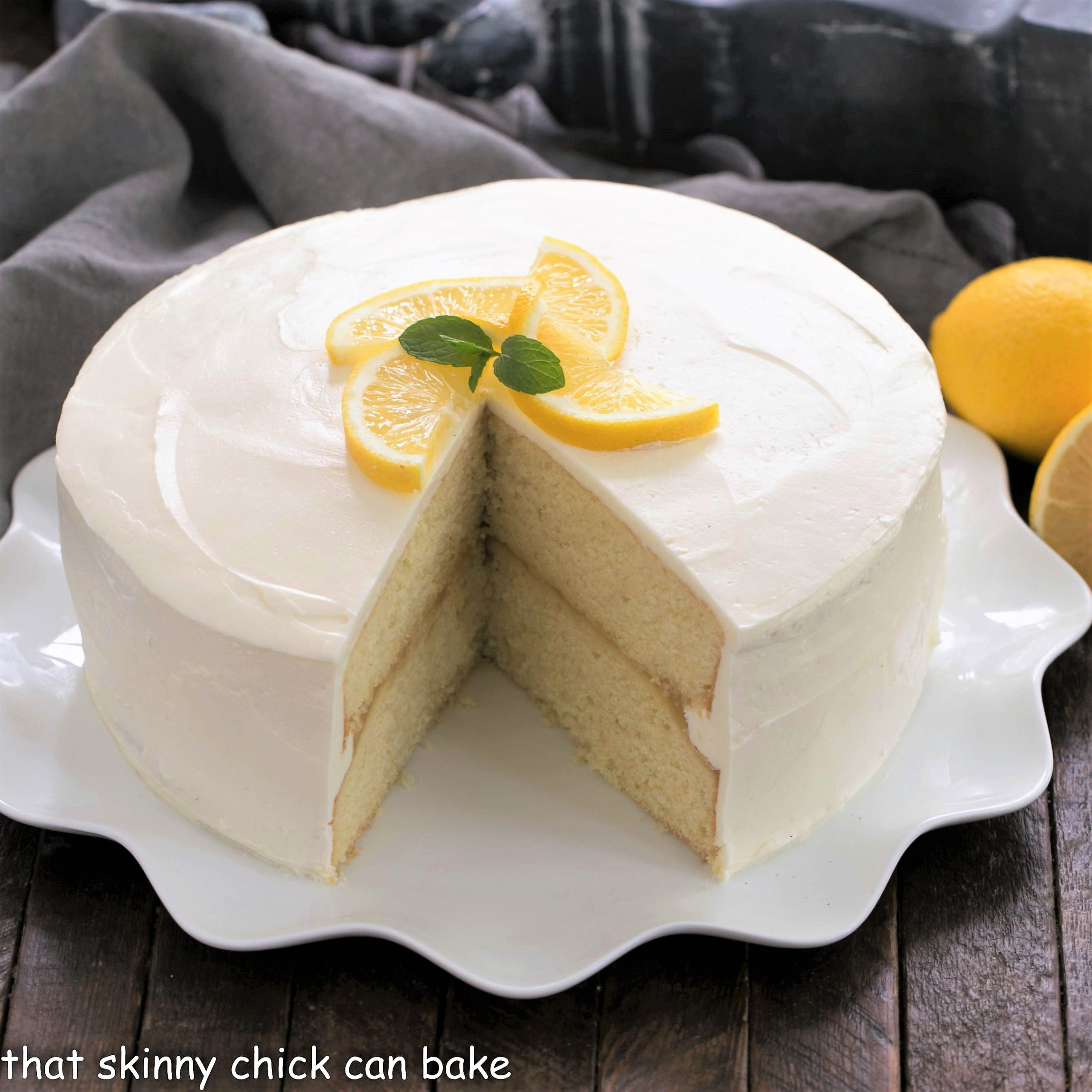 Lemon cake with a wedge cut out on a white platter