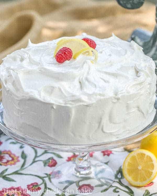 Lemon Layer Cake on a glass cake stand with lemon halves