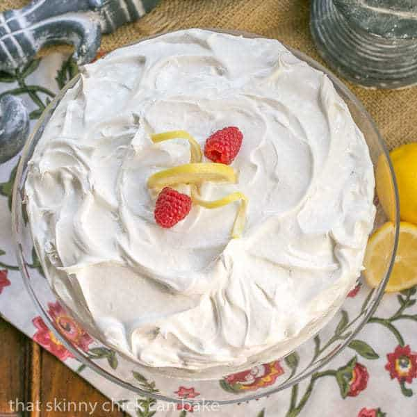 Overhead view of Lemon Layer Cake on a glass cake stand topped with berries and lemon peel