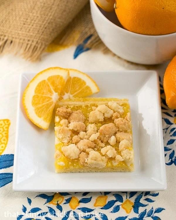 Meyer Lemon Streusel Bars on a white dish garnished with lemon slices