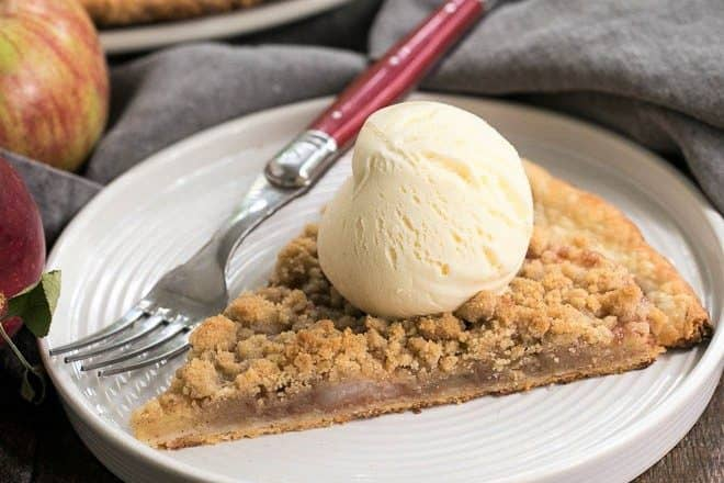 Apple Pie Pizza slice with a scoop of ice cream on a white dessert plate with a red handled fork in front of whole pizza