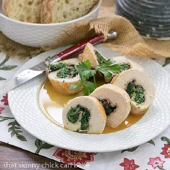 Chicken Saltimbocca Pinwheels on a white ceramic basket weave plate with a red knife