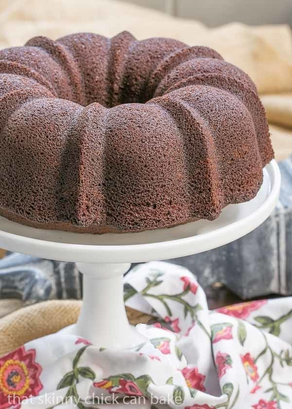 Chocolate Buttermilk Bundt Cake on a white ceramic cake stand with a floral napkin