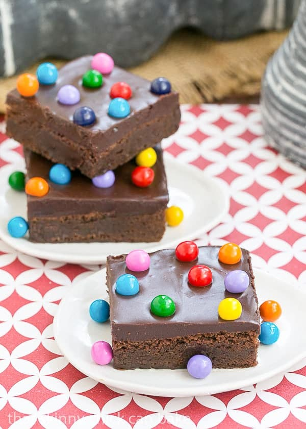 Cosmic Brownies stacked on white plate with colorful candy garnishes