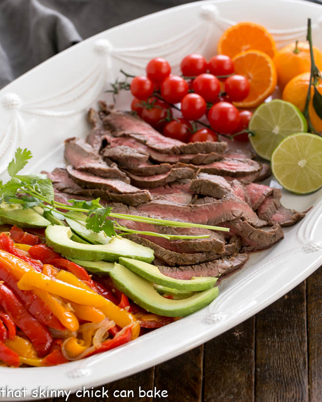 Flank Steak Fajitas and toppings on a white platter