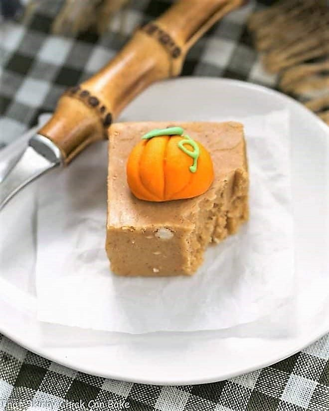 Easy Pumpkin Fudge on a white plate, topped with a candy pumpkin with a forkful removed