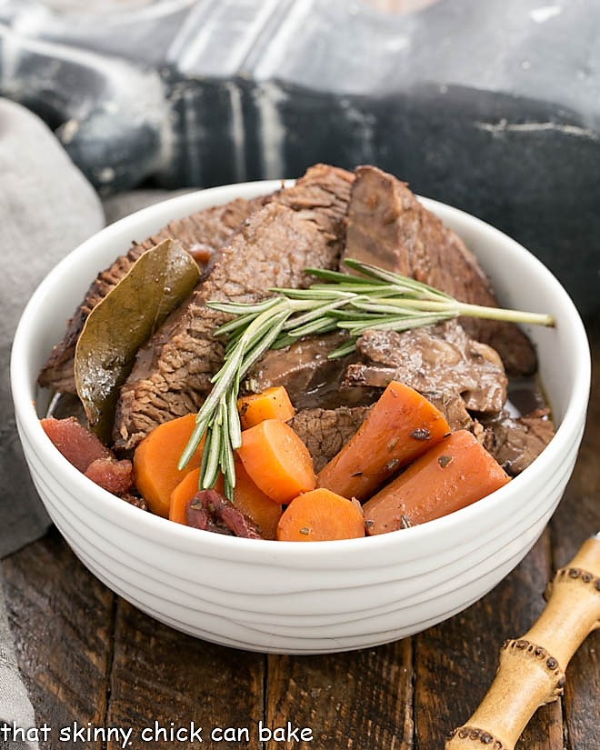 Beef brisket recipe in a white ceramic bowl with carrots and rosemary