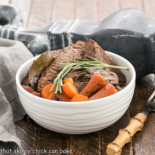 Rosemary Garlic Brisket in a white ceramic bowl and a sprig of rosemary