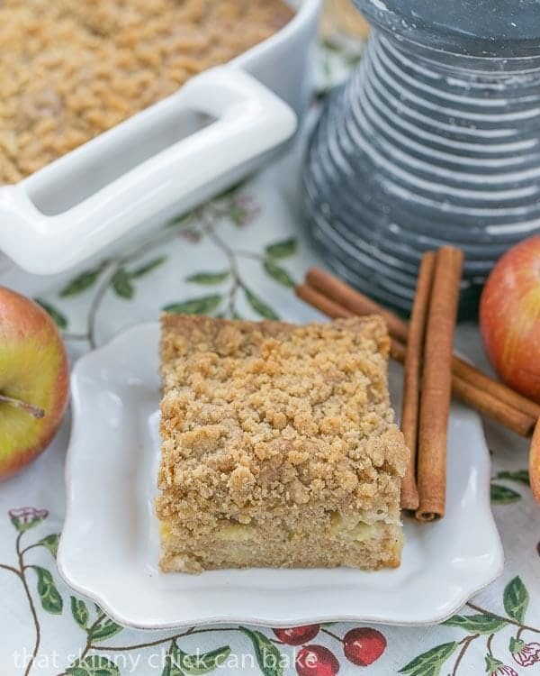 Apple Coffee Cake slice on a square white plate with cinnamon sticks