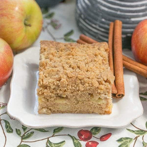 Apple Coffee Cake slice on a white plate surrounded by fresh apples and cinnamon sticks