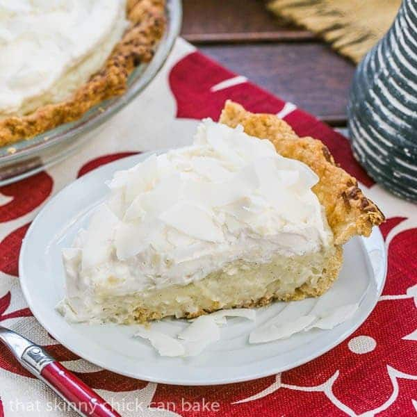 Coconut Cream Pie slice on a dessert plate on a red and white napkin