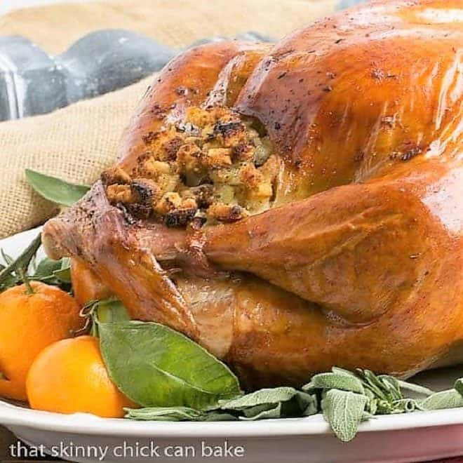 Dry Brined Turkey on a platter with herbs and oranges