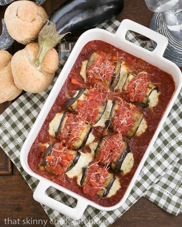 Eggplant Rollatini in a white casserole dish surrounded by wheat rolls and a whole eggplant