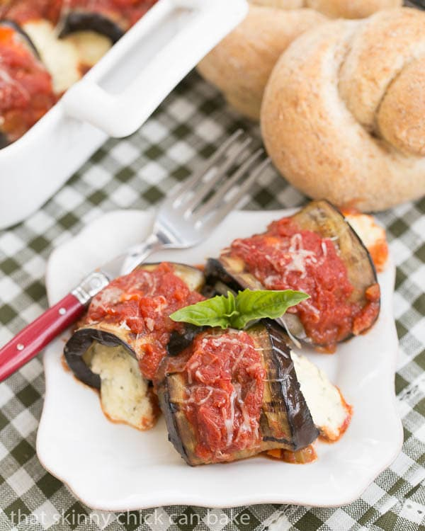 Eggplant Rollatini with Ricotta and Mozzarella on a square white plate garnished with fresh basil