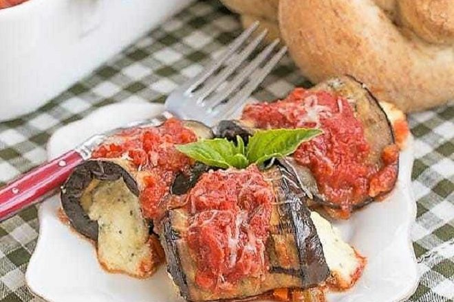 Eggplant Rollatini on a white dish with a red handled fork