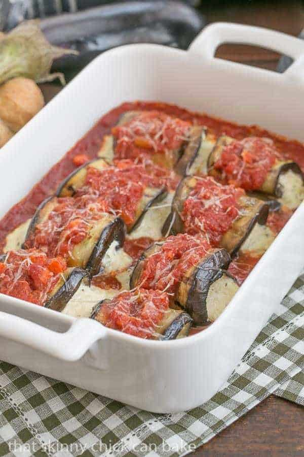 Eggplant Rollatini with Ricotta and Mozzarella lined up in a white casserole dish