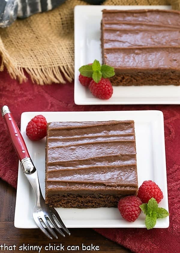 Chocolate Sheet Cake slices on a square white plates with raspberries