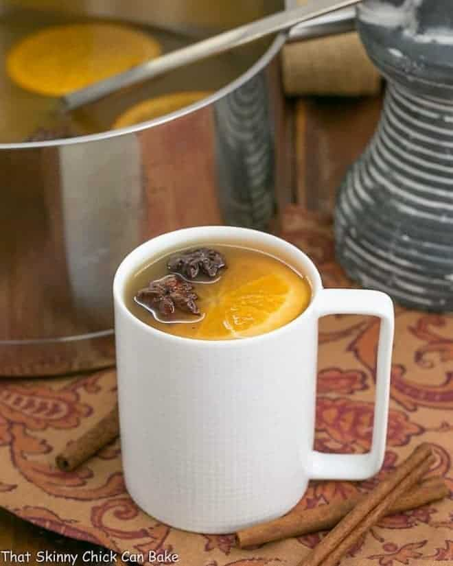 Mulled Apple Cider in a white mug with an orange garnish