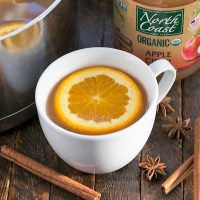 mulled apple cider in a white coffeed cup with cinnamon sticks